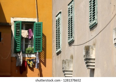 Traditional Mediterranean architecture in Sibenik, Croatia. Colorful wooden windows with drying clothes and plants. Sibenik is popular summe travel destination.