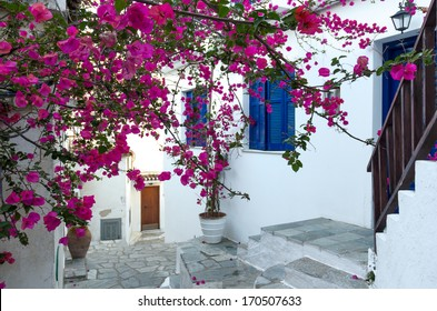 Traditional mediterranean house covered with pink flowers - Skiathos, Greece