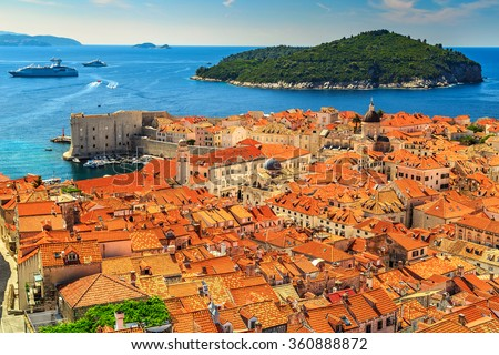 Traditional Mediterranean houses with red tiled roofs and rocky green idyllic island in background,Dubrovnik,Dalmatia,Croatia,Europe