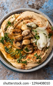 Traditional Mediterranean hummus with mushrooms and onions. Classic Hummus with paprika, olive oil, onions, mushrooms and seasonings. Closeup.