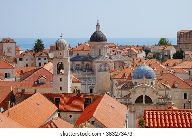 Traditional Mediterranean Old Town houses with red tiled roofs and rocky green idyllic island in background, Dubrovnik, Dalmatia, Croatia, Europe. Beautiful travel photo.