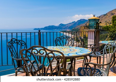 Traditional mediterranean seaside restaurant on the hillside with mosaic deacorated wrought iron tables and chairs and amazing blue sea panorama with clear blue sky, Sicily