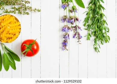traditional mediterranean spices and vegetables with uncooked pasta on white wooden table background