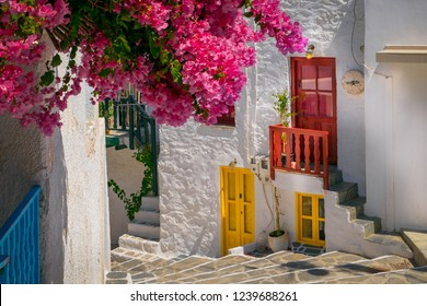 Traditional mediterranean street with white houses and colorful flowers and doors, Cyclades, Greece, Europe