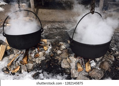 Traditional method of evaporating sap in two cast iron pots to produce maple syrup Kortright Centre for Conservation,  Woodbridge, Ontario, Canada - March 1, 2015