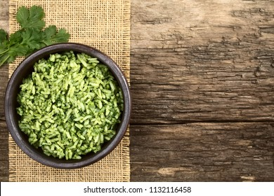 Traditional Mexican Arroz Verde green rice dish made of long-grain rice, spinach, cilantro and garlic, served in rustic bowl, photographed overhead with copy space (Selective Focus on the rice dish)