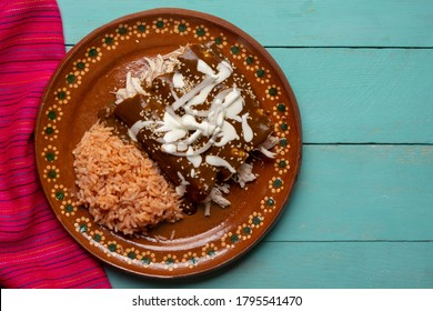 Traditional mexican chicken enchiladas with mole sauce and rice on turquoise background
