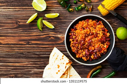 Traditional Mexican chili con carne served on a rustic wooden background in a pan with corn, mexican tortilla bread, lime and jalapeño. Top view. Space for text