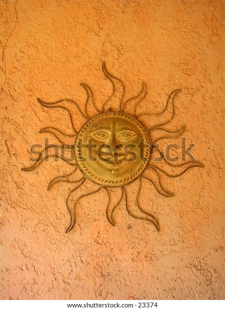 Traditional Mexican clay and iron sun face for the garden.