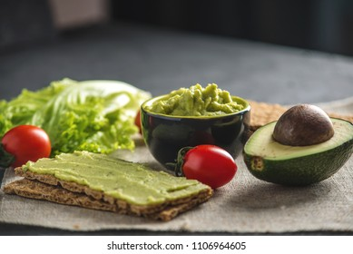Traditional Mexican cold appetizer made of pureed avocado pulp with bread and vegetables on the table. Concept healthy vegetarian Breakfast