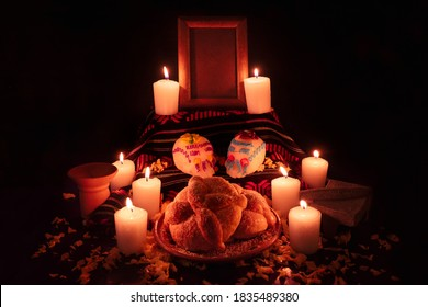 Traditional mexican day of the dead altar with bread and sugar skulls on dark background