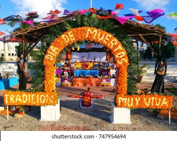Traditional Mexican Dia de los Muertos altar with sugar skulls, candles, fruit, family photos and decorative objects in Playa del Carmen, Mexico. The text says: Day of Dead - very live tradition