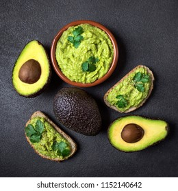 Traditional Mexican Dip Sauce Guacamole in a bowl with bread toasts,  whole and cut half avocado  on dark background. Top view. Copy space