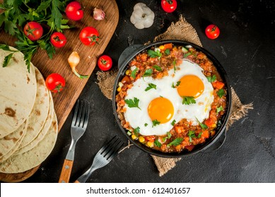 Traditional Mexican dish Huevos rancheros - scrambled eggs with tomato salsa, with taco tortillas, fresh vegetables and parsley. Breakfast for two. Top view. With a forks, copy space