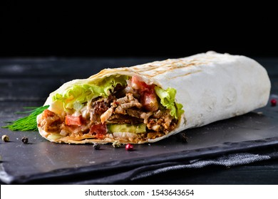 Traditional Mexican food, burritos with meat and beans, selective focus of beef steak burritos with vegetable