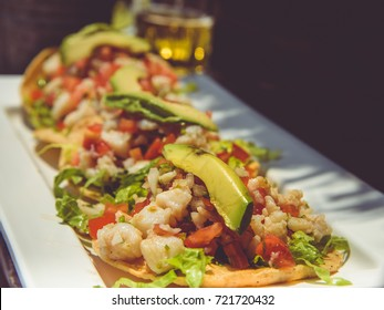 "Traditional mexican food ""tacos"" with glass of beer on the white table."