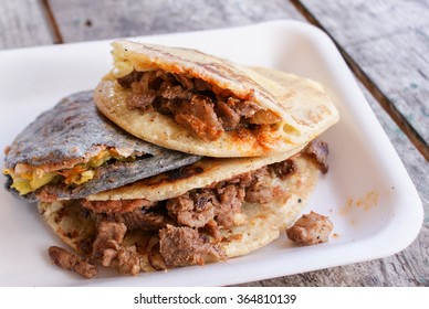 Traditional Mexican Gorditas - thick yellow or blue corn tortillas stuffed with cheese, veggies and meats. Shallow depth of field