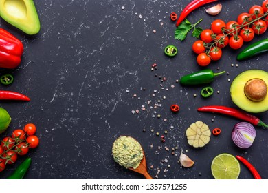 Traditional Mexican Guacamole sauce in spoon and ingredients on black stone table. Top view with copy space.
