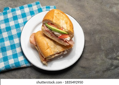 Traditional mexican ham sandwich with avocado and cheese also called torta on dark background