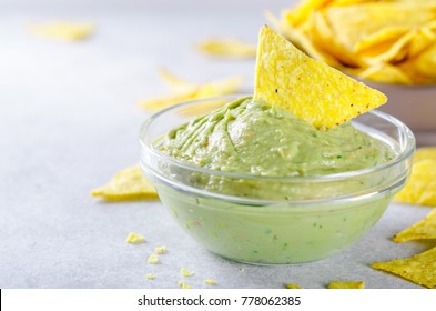 Traditional mexican homemade guacamole sauce in a glass bowl and a bowl with tortilla chips on a light stone background. Party food concept.  Front view, copy space, horizontal image