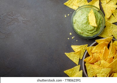 Traditional mexican homemade guacamole sauce in a glass bowl and a bowl with tortilla chips on a dark black stone background. Party food concept.  Top view, copy space, horizontal image