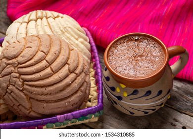Traditional mexican hot chocolate with sweet conchas bread on wooden background