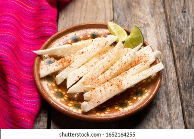 Traditional mexican jicama  cutted with chili powder on wooden background