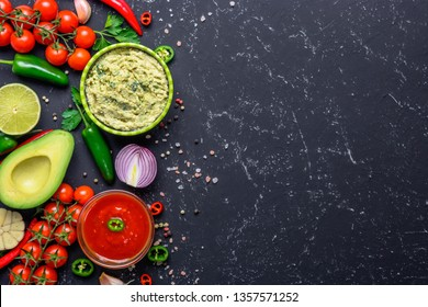 Traditional Mexican Latin American Salsa sauce and Guacamole and ingredients on black stone table. Top view copy space.