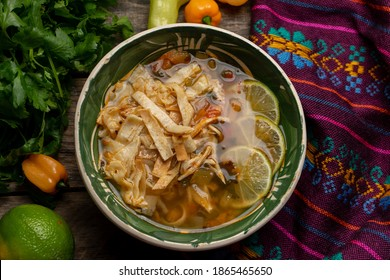 Traditional mexican lime soup with chicken on wooden background