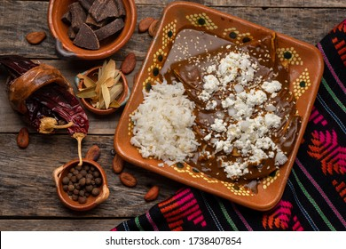 Traditional mexican mole enchiladas with rice on wooden background