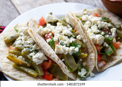 Traditional mexican nopal cactus tacos with cheese on wooden background
