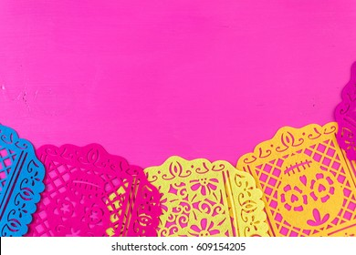 Traditional Mexican papel picado paper banner on a wood background.