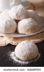 Traditional Mexican polvoron cookies with pecans and powdered sugar macro on the table. vertical