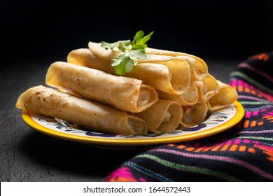 Traditional mexican potato and cheese fried tacos also called flautas on dark background