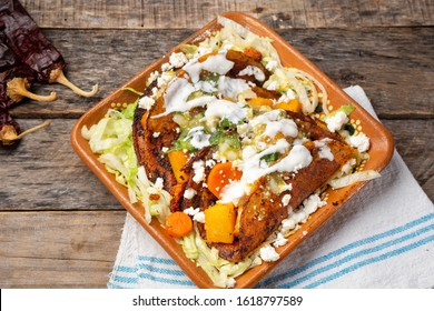 Traditional mexican red enchiladas with potato and pork chorizo also called Potosinas on wooden background