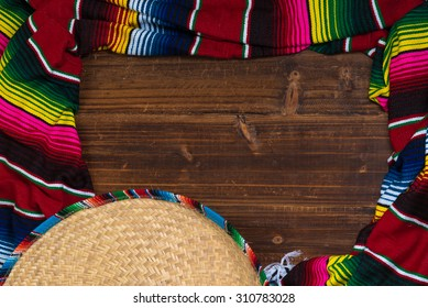 A traditional Mexican Sombrero and serape blanket on a wooden background with copy space