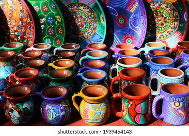 Traditional Mexican souvenirs. Multi-colored ceramic mugs and tableware in the gift shop. Selective focus.