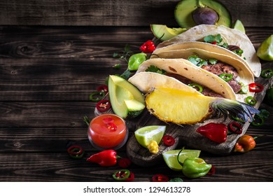 Traditional mexican street food - beef tongue tacos with ananas salsa and guacamole. Copy space background.