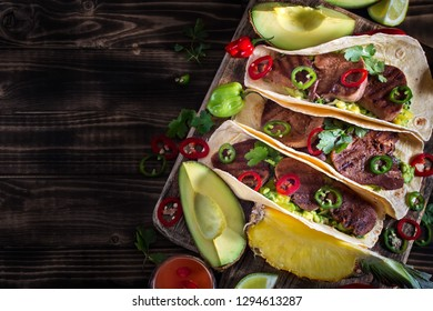 Traditional mexican street food - beef tongue tacos with ananas salsa and guacamole. Copyspace background.