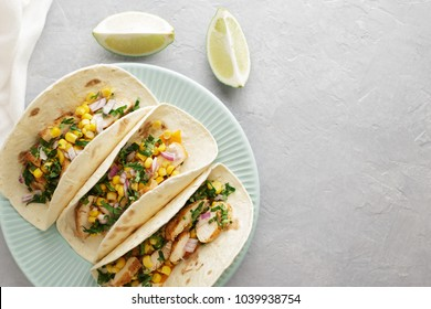 Traditional mexican tacos in blue plate on the gray stone background. Latin American fast food top view with copy space.