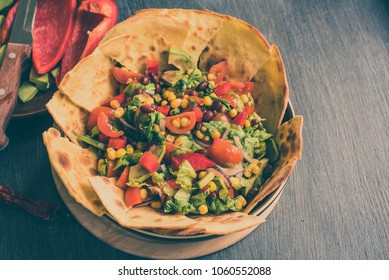Traditional Mexican vegetarian taco salad with avocado, corn, pepper, tomatoes and beans
