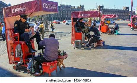 Traditional Mexico city street scene,street shoe shiners polish boots customers.City police officers  getting  shoeshine and reading newspapers before start of work on central square.Jan 2015,Mexico