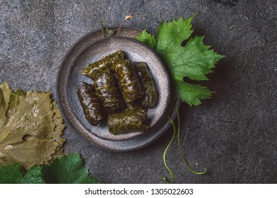 Traditional Middle Eastern dolma or tolma. Grape leaves stuffed with meat and rice. On Gray plate, gray concrete background