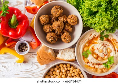 Traditional middle eastern homemade dishes falafel, pita, hummus and chickpea served with vegetables and spices on woodwn table. Top view