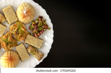 Traditional middle eastern mamoul cookies and assorted baklawa. Top view. Arabic baked sweets with nuts in white plate on dark wooden table with copy space. Ayd El Fithr feast cookies.