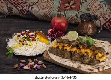 Traditional Middle eastern Persian chicken and lamb meat Shashlik Kebab (skewered meat) BBQ Grill on flat pita bread and saffron rice and tahchin and pomegranate on a dark background. Iranian cuisine
