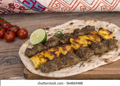 Traditional Middle eastern Persian chicken and lamb meat Shashlik Kebab (skewered meat) BBQ Grill on flat pita bread on a dark background. Iranian cuisine