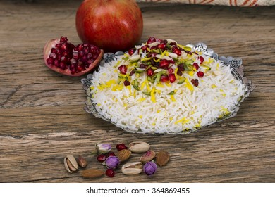 Traditional Middle eastern Persian saffron rice and tahchin, nuts and pomegranate on a wooden background. Iranian cuisine