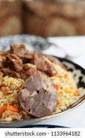 Traditional Middle Eastern pilaf rice with meat in plate on restaurant table