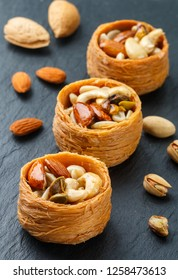 """Traditional middle Eastern sweets """"bird's nest"""" in honey syrup with nut filling - almonds, cashews, pistachios. Baklava close-up. Delicious dessert. Selective focus"""